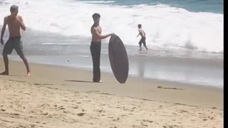 Guy in black jeans fails at jumping on surf board
