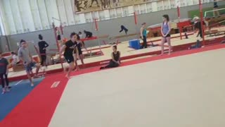 Gymnast does a flip on platform and falls, laughs