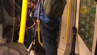 Man in blue plays flute on subway