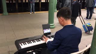 Man in blue suit plays piano in subway station
