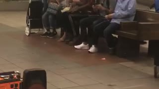 Guy red shirt black hat dancing sits between people subway bench - Video