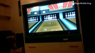 Guy green shirt slips while wii bowling strike