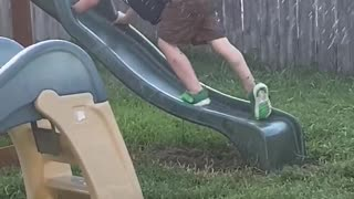 Kid Tries Climbing up Wet Slide