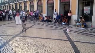 Toddler dances to drumming street performer