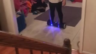 White shirt woman falls off hoverboard in front of stairs