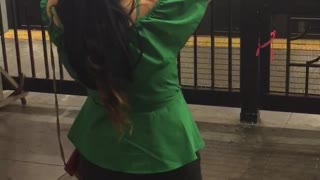 Girl in green shirt dancing in subway station