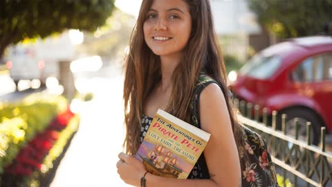 Happy Girl Walking in a Park Carrying a Book