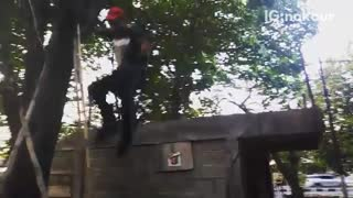 Guy in red hat jumps off roof lands on dirt - Video