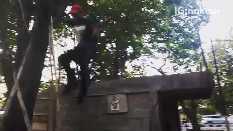 Guy in red hat jumps off roof lands on dirt