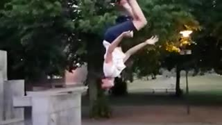 Guy slow motion backflip off of wall lands on butt bends arm - Video