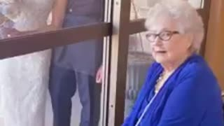 Bride visits her grandmother through glass on wedding day
