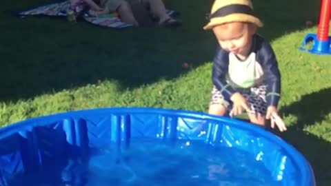 Little kid tries to walk blue kiddie pool but falls face first instead