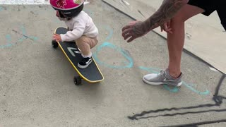 Young Girls Showcases Skateboard Skill with Dad's Help
