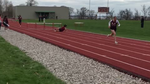 A girl in red falls off hurdle in high school track field