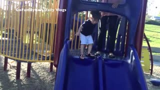 Unsuspecting Toddler zooms down the slide - Video