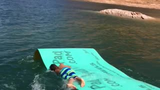Boy slides down boat slide bellyflop on blue mat