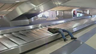 Sleeping man takes a ride on baggage claim - Video