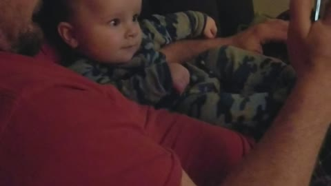 Baby finds his own video funny