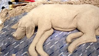 Street artists sculpts realistic sand