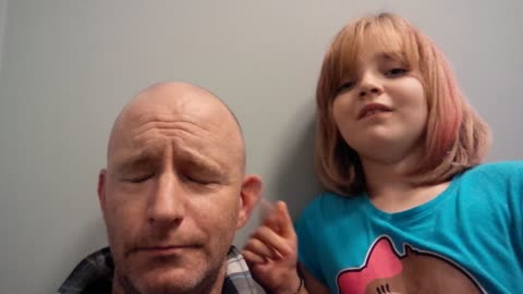 Bored little girl flicks dad's ear
