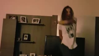 Music girl in white top dancing near tv nearly falls  - Video
