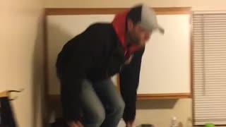 Guy red hoodie jeens boots jumps from kitchen counter onto table and tumbles over - Video