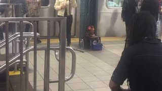 Woman sings man plays drums subway - Video