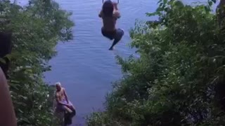Shirtless guy swinging from tree falls into water