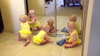 Triplets playing with mirror