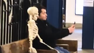 Man takes a selfie with skeleton sitting on bench in subway station