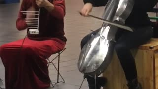 Silver skull and silver bird helmet playing cello violin in subway red dress black suit