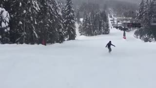 Black jacket snowboard guy falls on butt going down hill