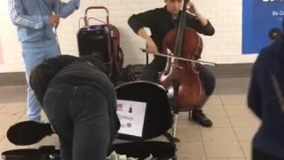 Homeless guy takes some money out of case of kids performing subway