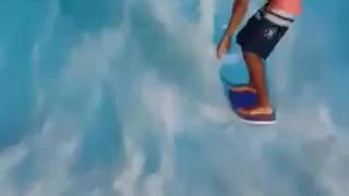 Shirtless guy surfs wave ride machine faceplants in water