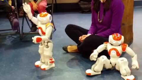 Two miniature robots dance to music