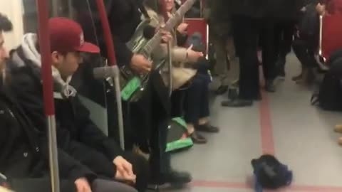 Two guys play electric guitar and violin on subway train