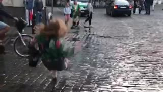 Woman in colorful jacket jumps in puddle and falls back - Video