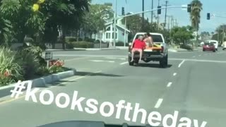 Red shirt guy riding on open trunk of truck