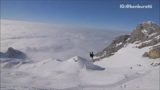 Guy in black backflips lands on back green skis