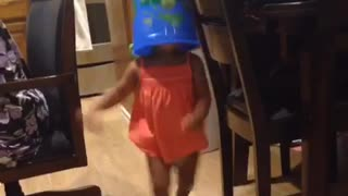Little girl in dress with blue bucket on head walking around house runs into table