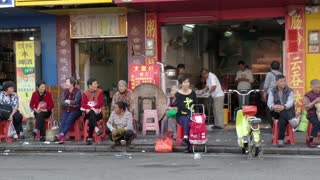Chinese Family Waiting In Street For Next Bus