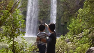 Father and child with watching the waterfalls