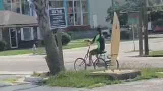 Guy riding bike with yellow board on back
