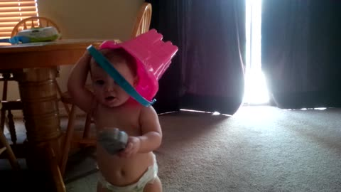 Toddler plays peek-a-boo with bucket on head