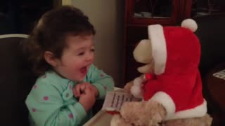 Precious toddler charmed by singing teddy bear