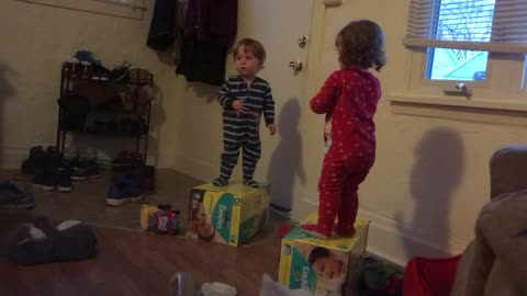 Twins engage in epic debate while standing on diaper boxes