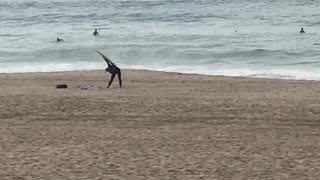 Guy uses surfboard to stretch on the beach