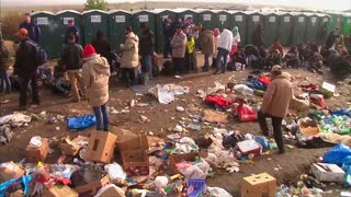 Migrants await buses at Hungarian holding center - Video