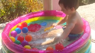 Playing babies with balls in the swimming pool