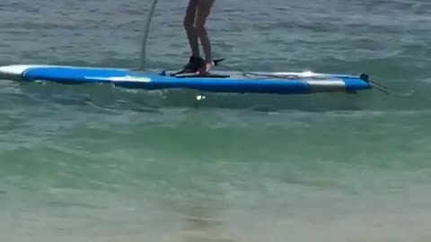 Surfboard peddle scooter beach guy